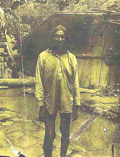 Unidentified man in front of traditional house
